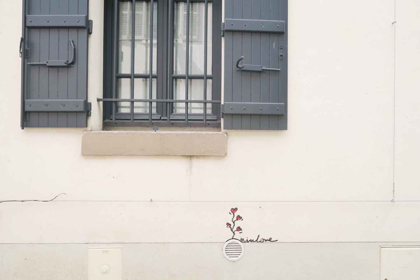 A Parisian window with grey shutters A row of Parisian houses on Monmarte in day trip to Paris on a budget on francescasophia.co.uk