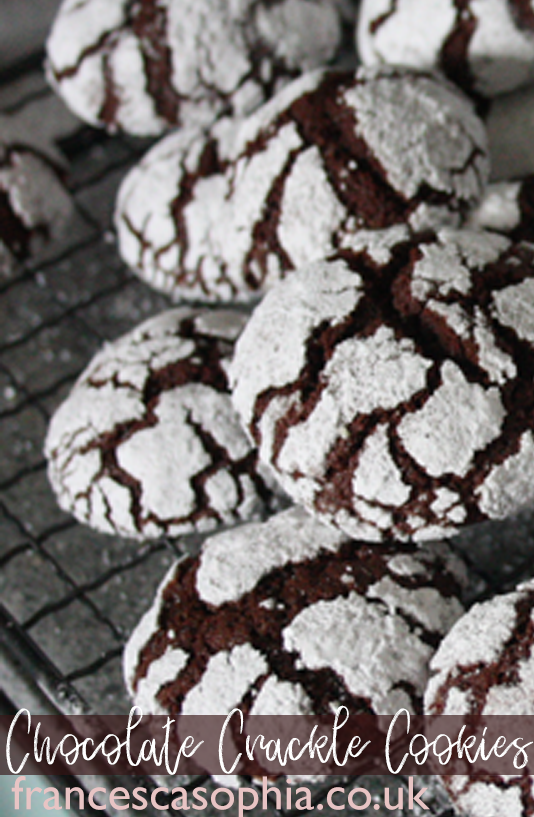 crackle chocolate cookies sitting on a cooling rack, in a pile