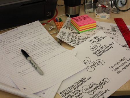 a desk full of brainstorms, notes, and post-it notes alongside a few pens