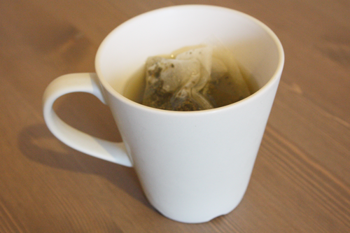cup of green tea with the tea bag still immersed