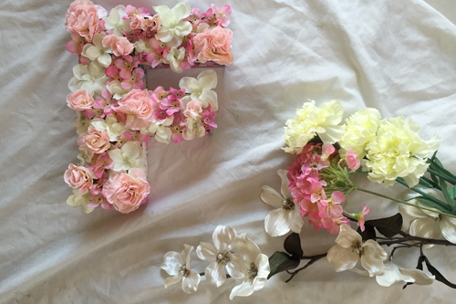 a floral letter 'f' sits on a white sheet, with a branch of silk flowers just beneath it