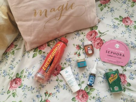 a bottle of lucozade, nuxe moisturising mask, tiger balm, vicks first defence, bath and body works pocketbac, a sephora eye mask, and some ginger ale, lying on a bed