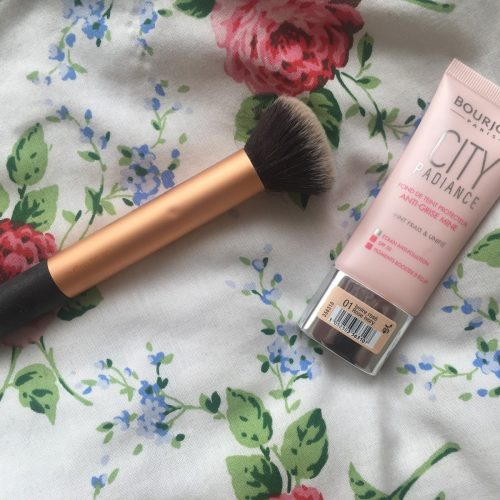 Bourjois City Radiance foundation packaging lying next to a real techniques buffing brush