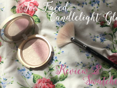 too faced candlelight rosey glow lying on a bed next to the zoeva fan brush