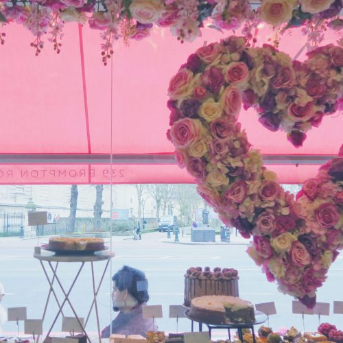 a heart shaped floral arrangement hangs in a window at the elan cafe, brompton road kensington on francescasophia.co.uk