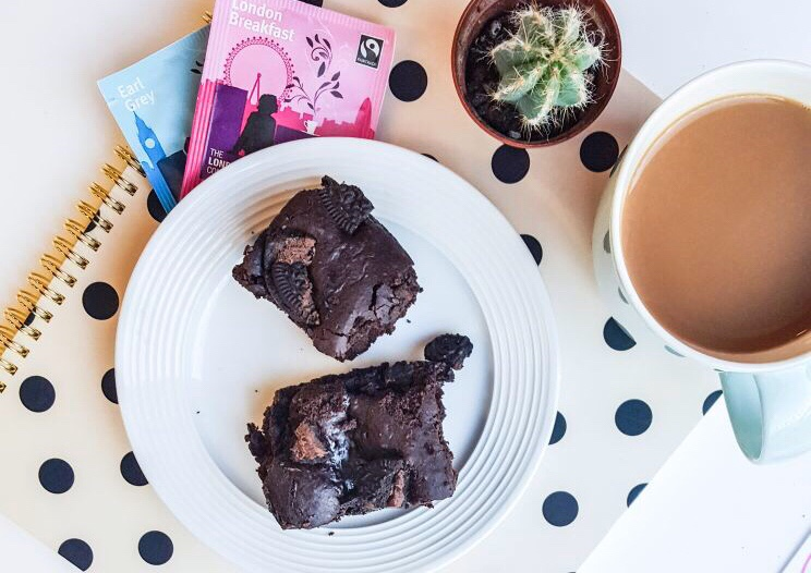 Vegan Oreo Brownies recipe on francescasophia.co.uk   a plate of vegan oreo brownies sitting on a polka dot notebook, next to a cup of tea, cactus, and two packets of tea
