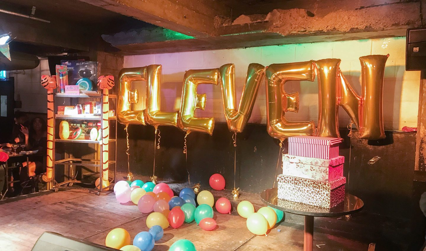 gold balloons which spell out eleven on a stage, surrounded by smaller balloons at Musical Bingo London Shoreditch Review on francescasophia.co.uk
