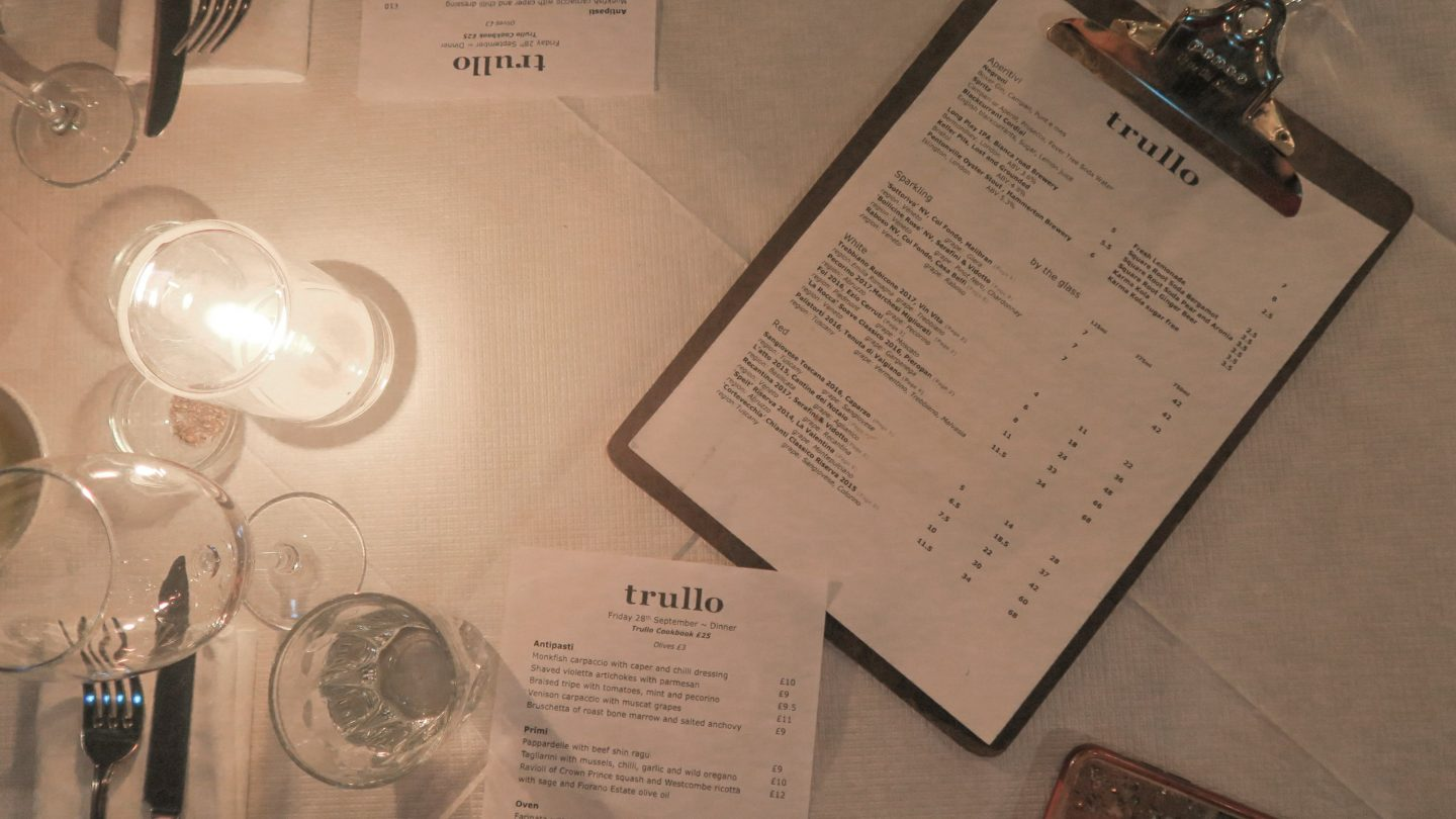 Menus spread on a table alongside a candle at Trullo London on francescasophia.co.uk