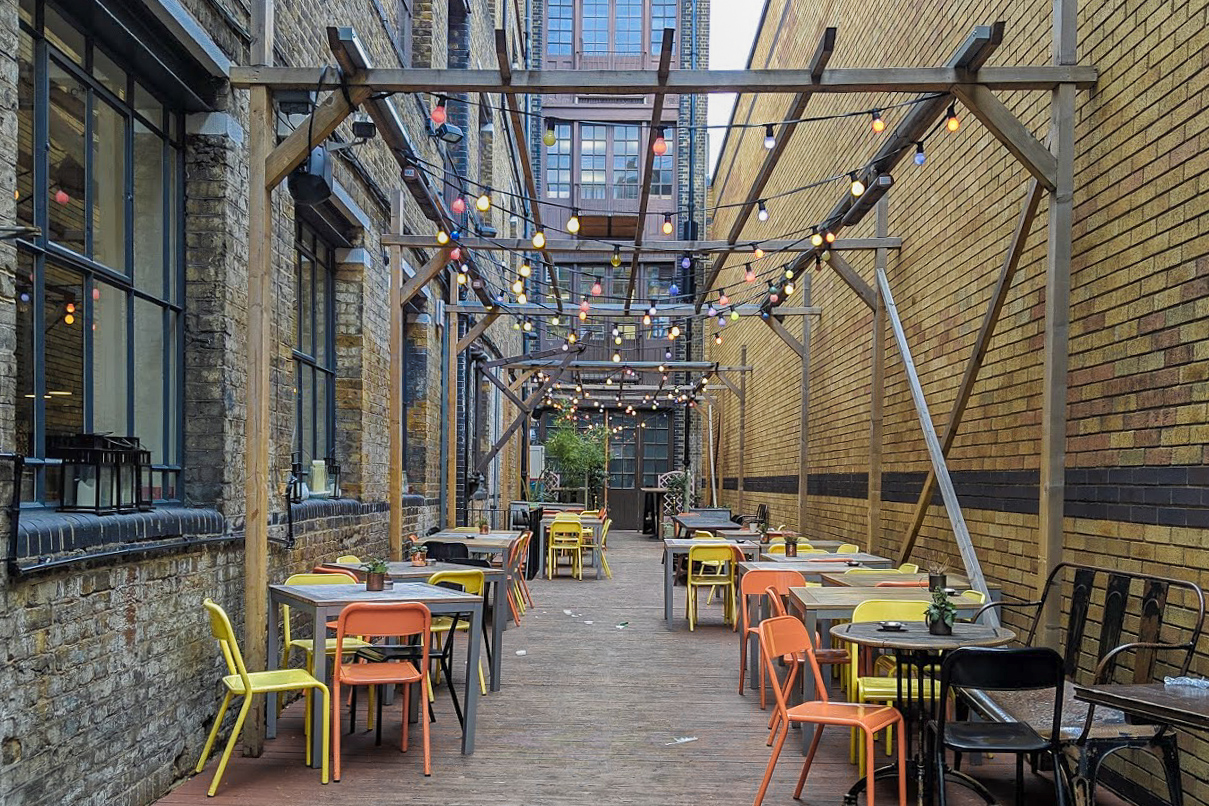 Outdoor seating area with orange and yellow chairs and hanging lights  in Things to Do in London Bridge on francescasophia.co.uk